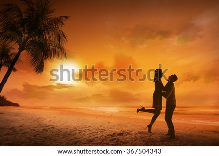 Young couple silhouette on a beach on sunset background - stock photo