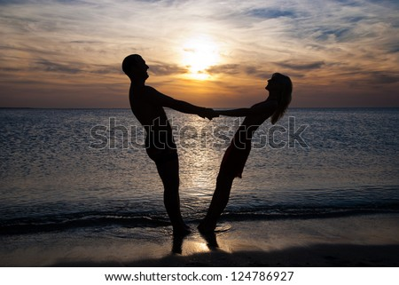 Young couple silhouette  on a sea beach holding hands and looking at sunset under the sea - stock photo