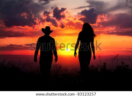 Young couple silhouette walking outdoors at sunset dramatic sky background. Man in cowboy hat and woman nearby - stock photo