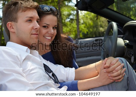 Young couple sits in a car, nestling their cheeks and holding hand in hand - stock photo