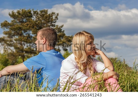 Young couple sits on summer green grass. - stock photo