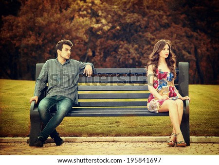 Young couple sitting apart on the bench in the park  - stock photo