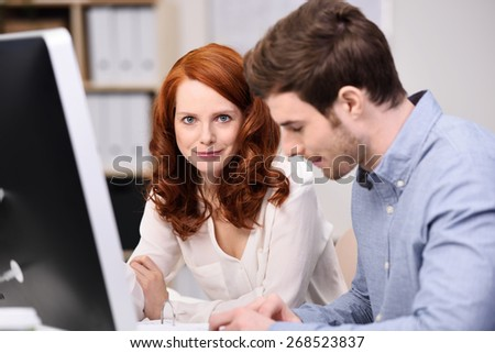 Young couple sitting at a desktop computer working together in the office with focus to the attractive redhead woman who is looking at the camera with a smile - stock photo