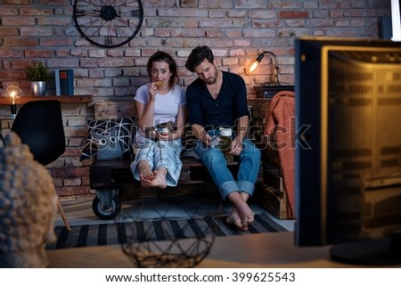 Young couple sitting at home on pallet furniture, watching tv, boring program. - stock photo