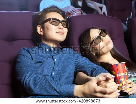 Young couple sitting at the cinema wearing 3d glasses, watching a film. Cinema photo series - stock photo