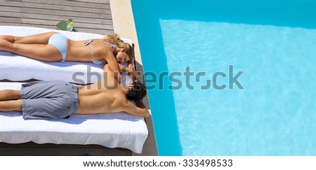 young couple sitting at the deck chairs by the pool  - stock photo