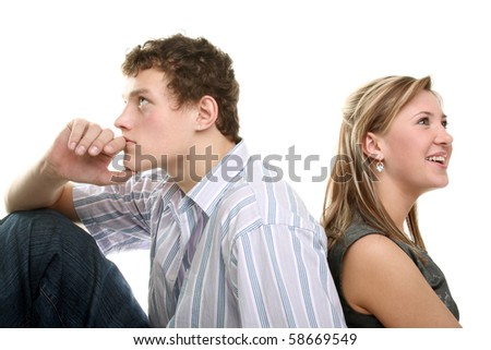 young couple sitting back to back - stock photo