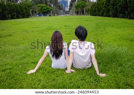 Young couple sitting back to camera on the grass - stock photo