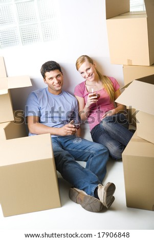 Young couple sitting between cardboard boxes and drinking wine. They're smiling and looking at camera. Front view. - stock photo