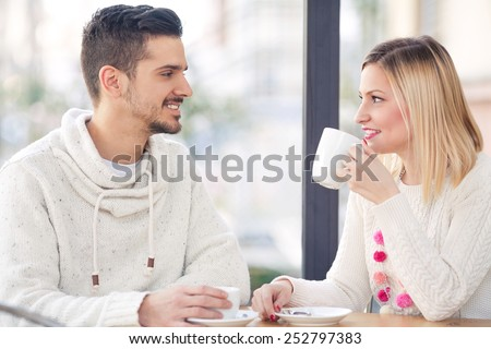 Young couple sitting in a cafe drinking coffee and tea - stock photo