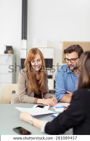 Young couple sitting in a meeting with an agent looking at a document together that she is presenting to them, view over the agents shoulder - stock photo