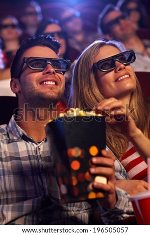 Young couple sitting in auditorium of multiplex movie theater, watching 3D movie, eating popcorn, smiling. - stock photo