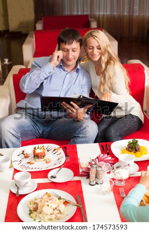 Young couple sitting in cafe. Man and woman in restaurant choose menu - stock photo