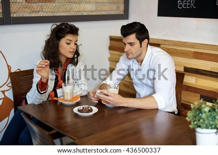 Young couple sitting in cafeteria, using mobilephone, having coffee and biscuit. - stock photo