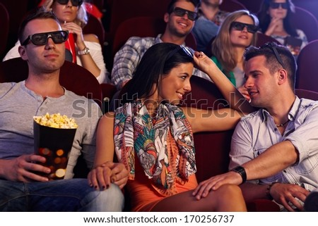 Young couple sitting in movie theater, girl flirting with boy on next seat. - stock photo