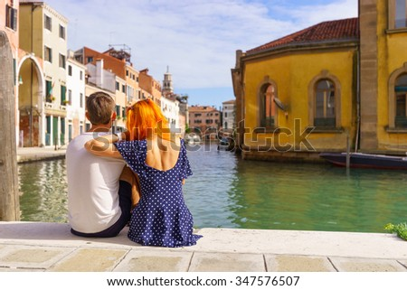 Young couple sitting in the border of canal in Venice. - stock photo