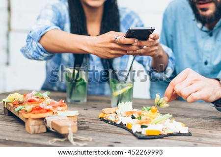 Young couple sitting in the restaurant and taking pictures of the food with mobile phone - stock photo