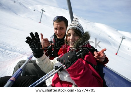 Young couple sitting on a chairlift - stock photo