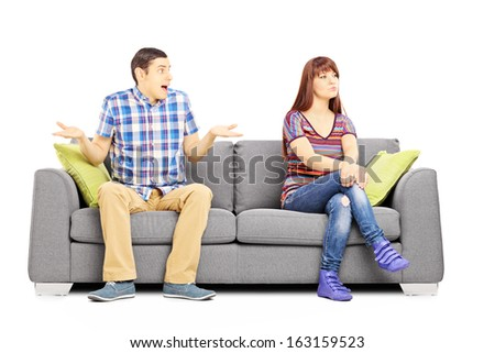 Young couple sitting on a couch during an argument isolated on white background - stock photo