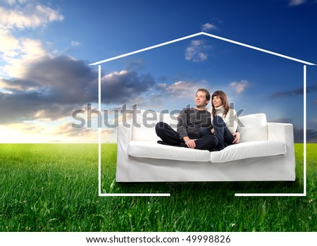 Young couple sitting on a couch on a green meadow surrounded by the form of a house - stock photo