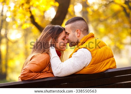 Young couple sitting on a park bench on a sunny autumn day and expressing tenderness - stock photo