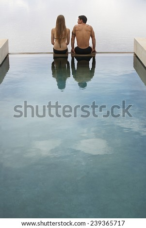 Young Couple Sitting on a Pool Edge - stock photo