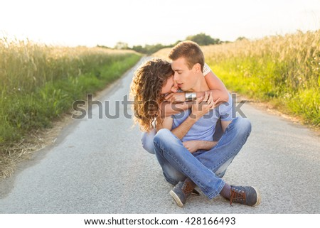 young couple sitting on a road and embracing - stock photo