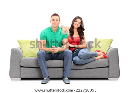 Young couple sitting on a sofa isolated on white background - stock photo