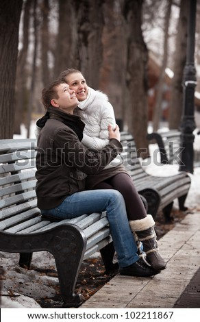 Young couple sitting on bench in winter park and looking up - stock photo