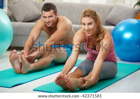 Young couple sitting on fitness mattress and streching legs before treining - stock photo