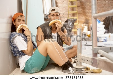 Young couple sitting on floor after daily work on renovating home, making sad face from crescent roll. - stock photo