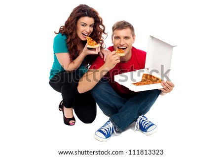 Young couple sitting on floor and enjoying yummy pizza - stock photo