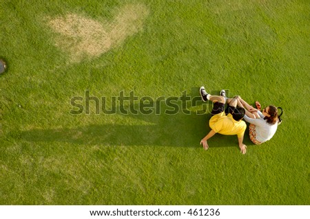 Young couple sitting on grass - stock photo