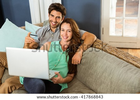 Young couple sitting on sofa and doing online shopping in living room - stock photo