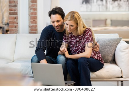 Young couple sitting on sofa and using laptop. Happy young relaxed couple working on computer at modern home interior. Happy woman and smiling man sitting on couch and using laptop.  - stock photo