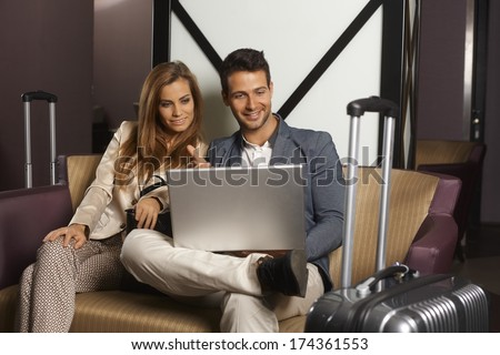 Young couple sitting on sofa at hotel lobby upon arrival, using laptop computer, smiling happy. - stock photo