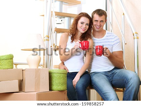Young couple sitting on stairs in new house - stock photo