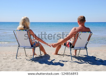 Young couple sitting on the beach chair on the sea beach and looking at see surface - stock photo