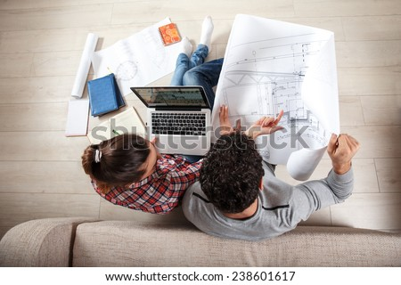 Young couple sitting on the floor and looking at the blueprint of new home.Investment. - stock photo