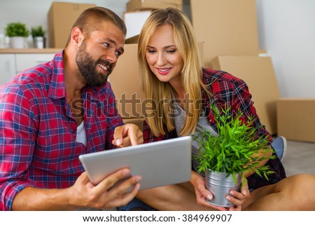 Young couple sitting on the floor with tablet pc and choosing furniture to their new apartment - stock photo