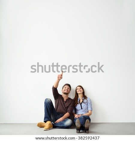 Young couple sitting on the ground leaning against an exterior white all with copy space pointing up into the air and smiling - stock photo