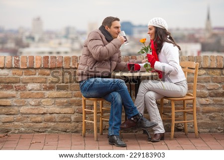 Young couple sitting outdoors on a Valentine's day - stock photo