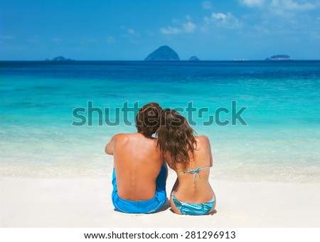 Young couple sitting together on a sandy tropical beach and looking to a horizon - stock photo