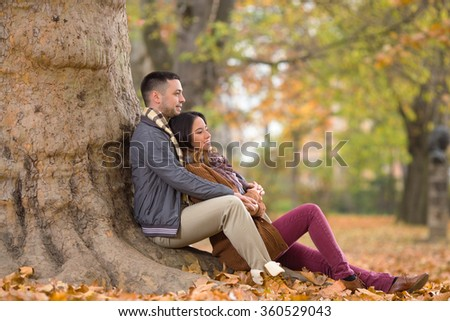 Young couple sitting under the tree in nature - stock photo