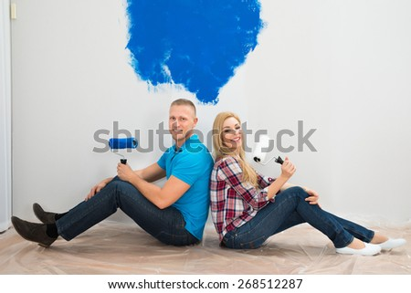 Young Couple Sitting With Back To Each Other On The Floor Near The Blue Painted Wall - stock photo