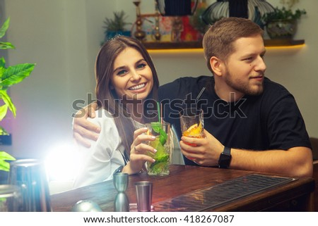 young couple sitting with cocktails at the bar talking and smiling - stock photo