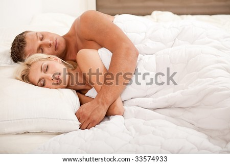 Young couple sleeping and hugging on bed - stock photo
