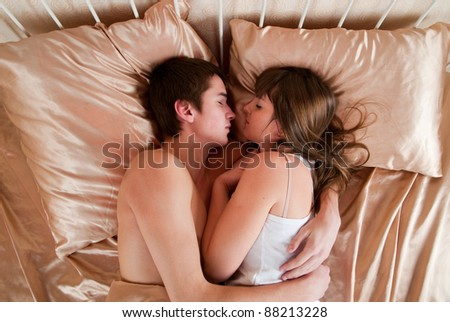 Young couple sleeping in a bed - stock photo