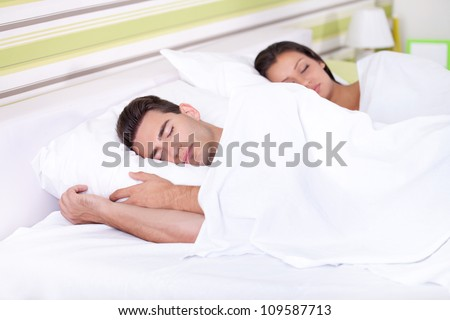 Young couple sleeping together in bed. A sensual and cute couple. - stock photo
