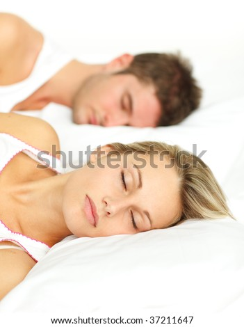 Young couple sleeping together in bed with focus on woman - stock photo